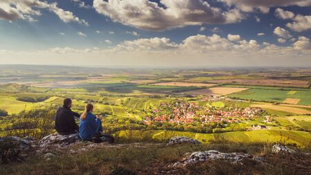 Two people (couple - man and woman) sitting on mountain on stone and looking into valley on beautiful autumn landscape with village, vineyards and fields. Blue sky, white clouds. Palava, Czech Reklamní fotografie