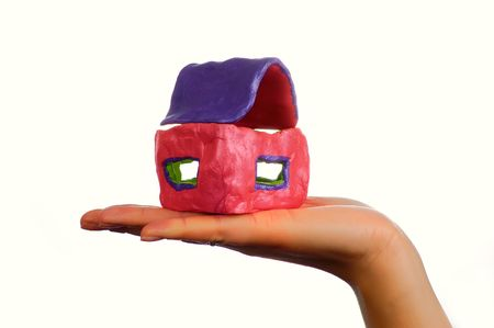 mortage: The colour little clay house on the female hand Stock Photo