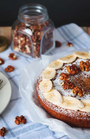 Angle view of cake with sliced banana, walnut and powdered sugar and glass jar full of nuts. Cozy still life in light tones on background with checked kitchen towel. Stock Photo