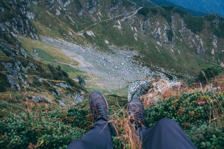 Man legs, sitting on edge of gorge. Point of view, focus on background, Carpathian mountains, Marmarosh
