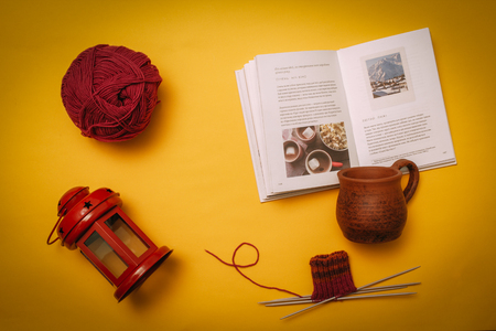 Hygge flat lay with cup, book, knitting needles and tangle, candlestick. Flat lay on yellow background