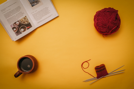 Hygge flat lay with cup, book, knitting needles and tangle. Flat lay on yellow background copy space