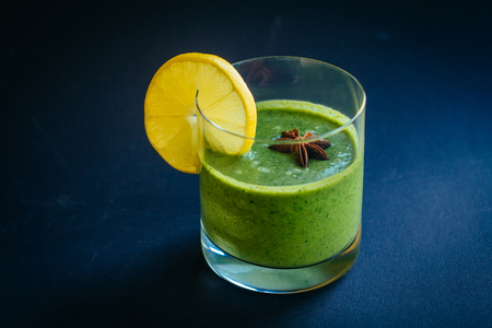 Raw smoothie green color with celery, cucumber and spinach. Close up glass