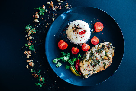 Basmati rice, chili pepper, cherry tomatoes and chiken steak. Dark background, black plate, top point Banco de Imagens