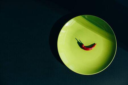 Chili pepper in green plate. Black background