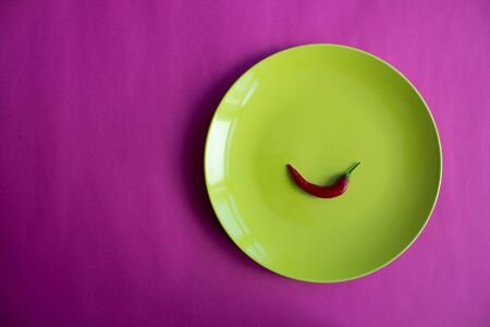 Chili pepper in green plate. Pink background