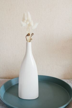 Dry flowers in ceramic white vase. Scandinavian style. Beige wall background