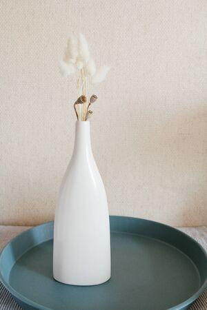 Dry flowers in ceramic white vase. Scandinavian style. Beige wall background