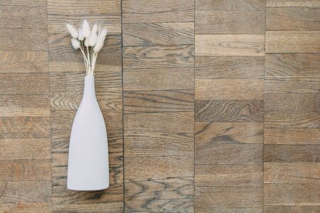 Bouquet of dried flowers in white ceramic vase on vintage wooden planks, top view horizontal