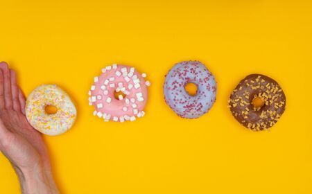 Sweet chocolate donut on yellow background and male hand. Dessert food