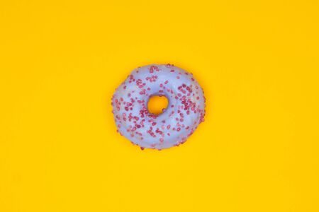 Sweet blue donut on yellow background. Dessert food Banco de Imagens