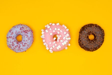 Sweet donuts on yellow background. Dessert food Banco de Imagens