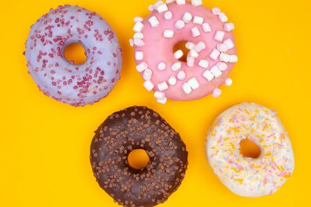 Sweet chocolate donuts on yellow background. Dessert food Banco de Imagens