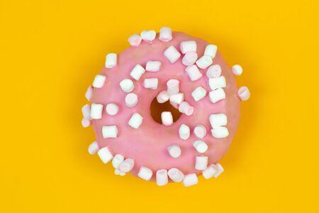 Sweet pink donut on yellow background. Dessert food