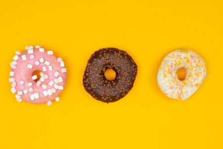 Sweet chocolate donut on yellow background. Dessert food Banco de Imagens
