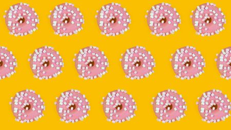 Pattern of sweet donuts on yellow background. Sweet tasty food, top view.