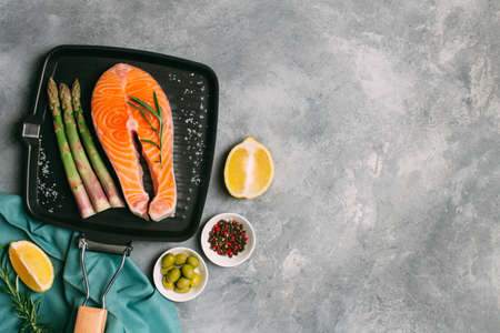 Raw salmon steak on grill pan with the addition of rosemary, aromatic spices, asparagus. Seafood restaurant background with copy space. Banco de Imagens