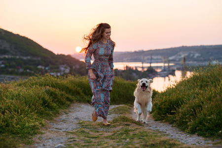 Beauty woman with her dog playing outdoors.