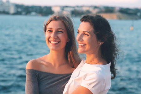19 years old: Portrait of happy mother with teenage daughter. Sunset light. Mom holding her teen daughter.