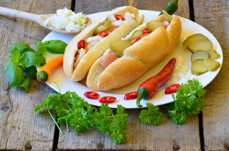 wiener dog: Hot dog with chilli on white plate with wood background