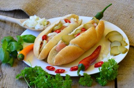 chiles picantes: Perrito caliente con chile, pimientos, cebolla deportivas y pepinos en un plato blanco con fondo de madera
