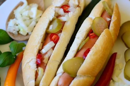 chiles picantes: Perrito caliente con chile, pimientos, cebolla deportivas y pepinos en un plato blanco Foto de archivo