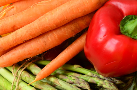 Peppers, asparagus and carrots in wooden box photo