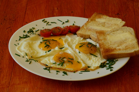 sunny side: Sunny side up eggs with chives, cherry tomatoes and roasted bread with butter on red background