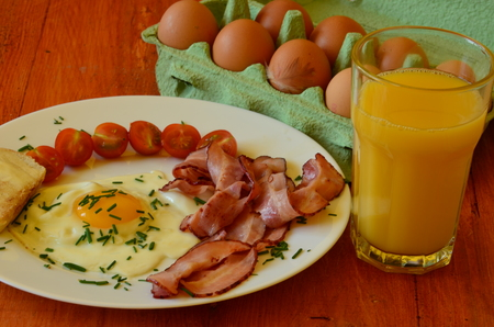 sunny side: Sunny side up eggs with chives, cherry tomatoes and roasted bread with butter and the glass of orange juice on red background