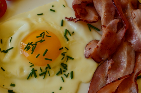 sunny side: Sunny side up eggs with chives and roasted slices of bacon