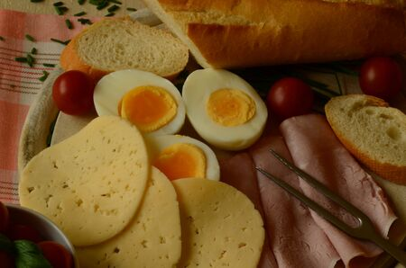 salami: Cooked eggs, slices of salami and cheese with baguette and cherry tomatoes Stock Photo