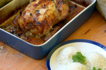 roasting pan: Roasted chicken in rustic roasting pan on wooden background