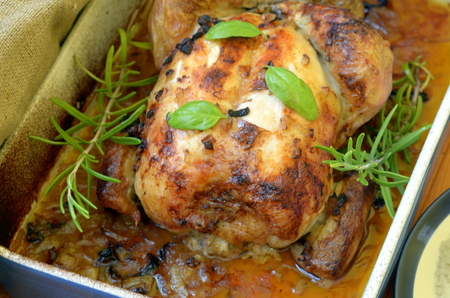 Roasted chicken with herbs in rustic roasting pan on wooden background