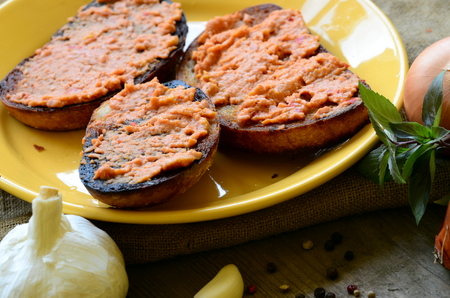 uk cuisine: Fried bread with spread and onion, basil, pepper and clove of garlic Stock Photo