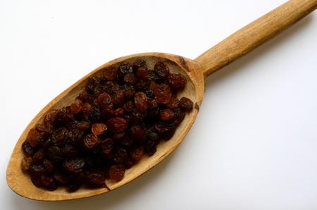 Golden raisins in wooden spoon on white background