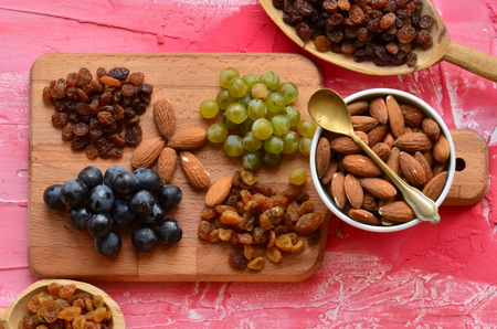 Various raisins, vine berries and almonds on chopping board