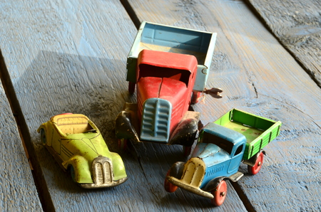 peddle: Vintage trucks (lorries) toys and covertible toy car on blue wooden background.