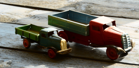 peddle: Set of vintage toys - trucks (lorries) toys on blue wooden background.