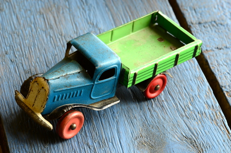 peddle: Vintage truck (lorry) toy on blue wooden background. Stock Photo