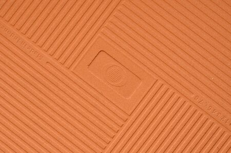 reverse: Brown embossed reverse side of small tile Stock Photo