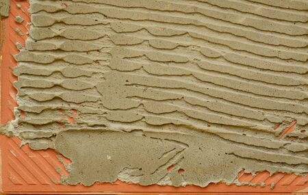reverse: Embossed reverse side of small tile with dry plastering