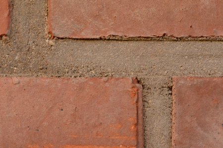 gaps: Red brick wall. Closeup with grey strong gaps.