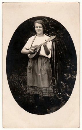 mandolin: GERMANY - 1930s: Vintage photo shows a woman plays mandolin outdoors. Photo is oval shape. Black & white antique photo.