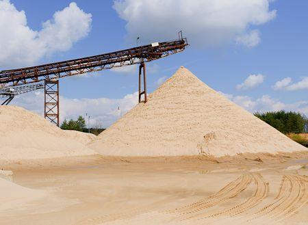 コンベヤー ベルトおよび砂のヒープ。建設業界。砂の採石場。水平方向の写真。 写真素材
