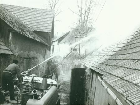 fireman: THE CZECHOSLOVAK SOCIALIST REPUBLIC - CIRCA 1980s: Retro photo shows fireman stands on the top of fire truck. Fireman demonstrates fire hose handling during a damage control exercise. Vintage black & white photography.