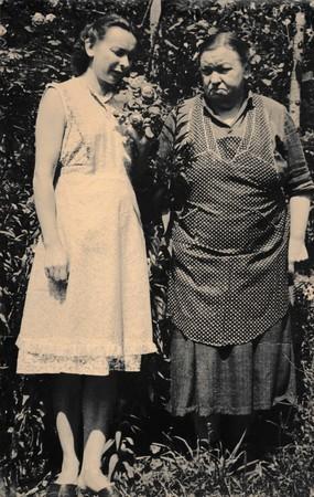 snapshots: THE CZECHOSLOVAK SOCIALIST REPUBLIC - CIRCA 1960s: Retro photo shows two women stand in the garden. Black & white vintage photography