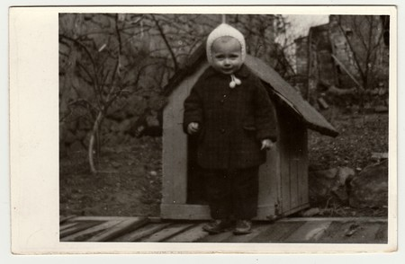 THE CZECHOSLOVAK REPUBLIC, CIRCA 1942: Vintage photo shows a small girl and kannel (doghouse), circa 1942.