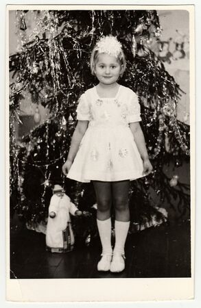 USSR - CIRCA 1980s: Vintage photo shows a small girl (about 7 years old) in front of Christmas tree. Editöryel
