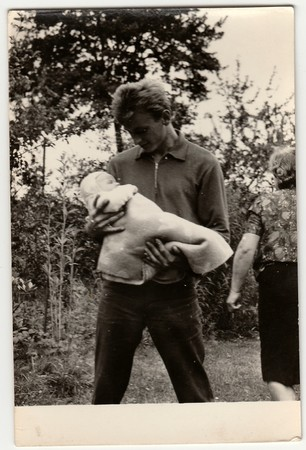 cradling: THE CZECHOSLOVAK SOCIALIST REPUBLIC - CIRCA 1960s: Vintage photo shows young man cradles baby.