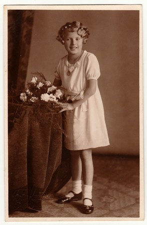 bbl: LIBEREC (REICHENBERG), THE CZECHOSLOVAK REPUBLIC - CIRCA 1930s: Vintage photo shows young girl with bouquet poses in a photography studio. Photo with dark sepia tint. Black & white studio portrait.